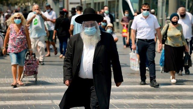 Un judío ortodoxo camina con barbijo en una calle de Jerusalén, este viernes. El país analiza una nueva cuarentena. Foto: AFP